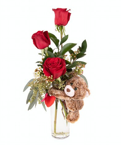 Red rose arrangement with a bear